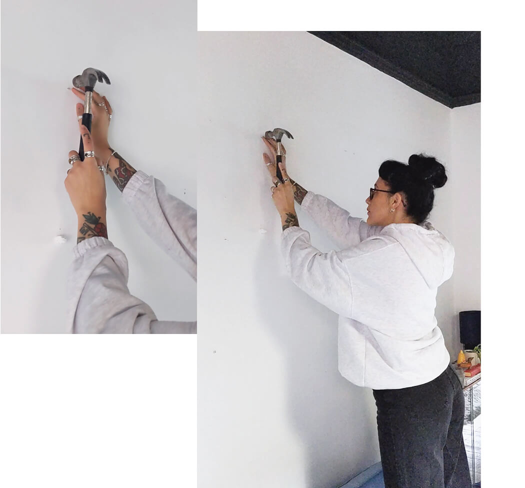 hammering a nail in the wall to hang a gallery wall