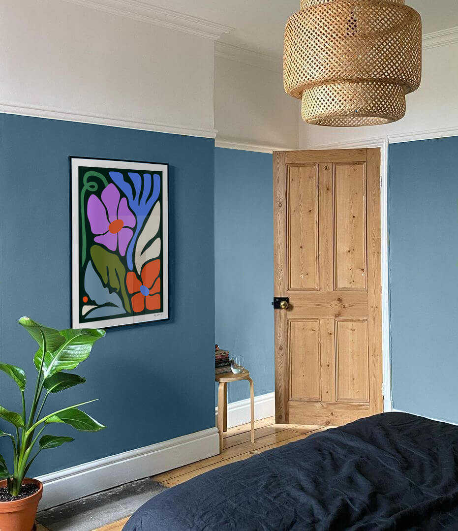 large framed art print hung on a blue wall